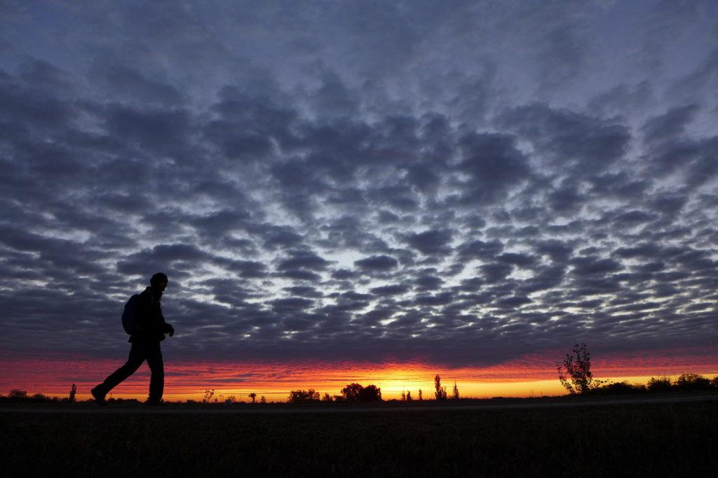 Turista gyalogol egy úton napfelkeltekor
