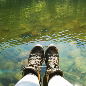 Eszter Barbara Borbála bakancsos lába egy tó partján