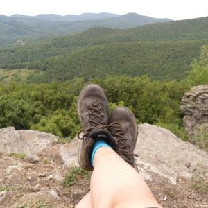 Jóri Éva lába túrabakancsban, a háttérben hegyekkel