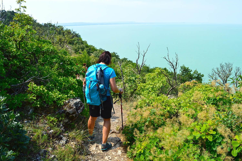 Hátizsákos turista egy ösvényen, háttérben a Balatonnal