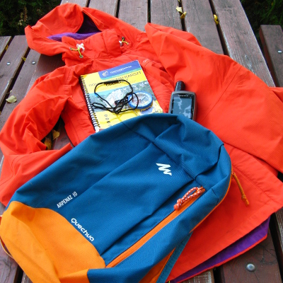 Esőkabát, hátizsák, térkép, tájoló és GPS egy asztalon