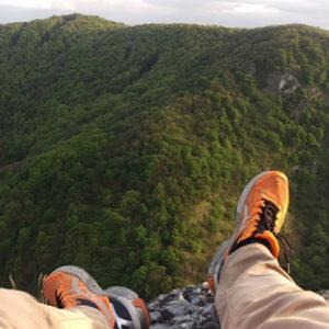 Varga Sándor sárga sportcipős lába a háttérben hegyekkel