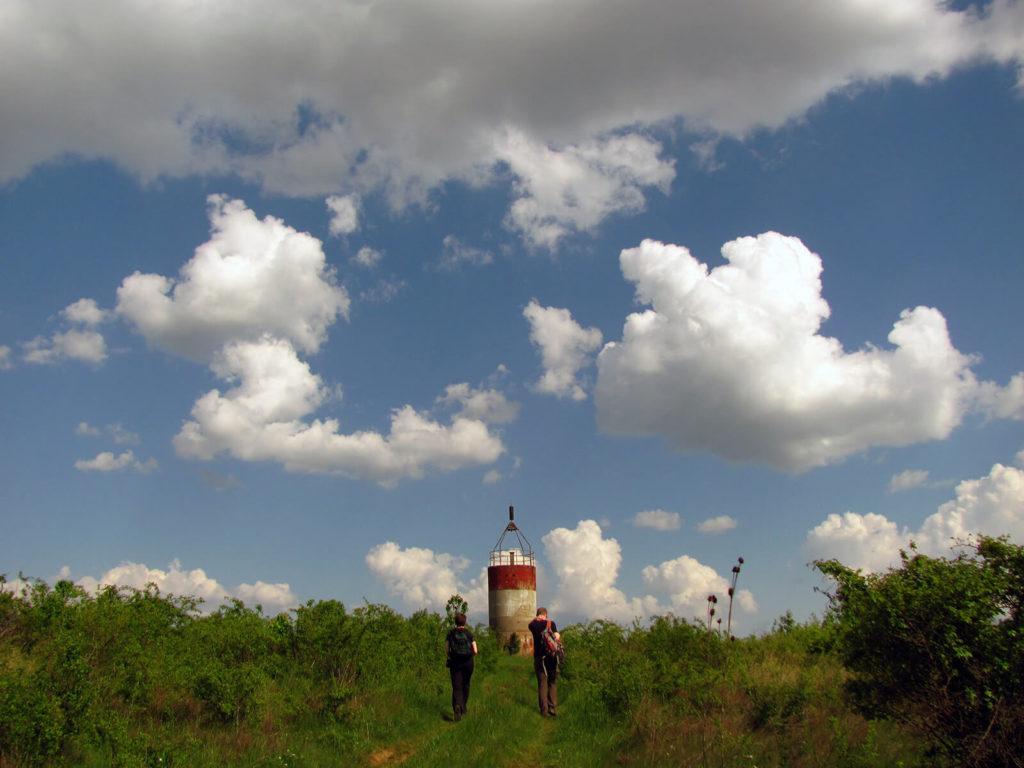 Két turista gyalogol egy geodéziai torony felé