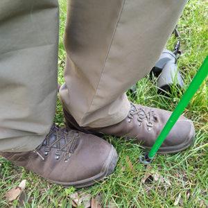 Tóth András bakancsos lába egy zöld túrabottal és egy távcsővel a fűben
