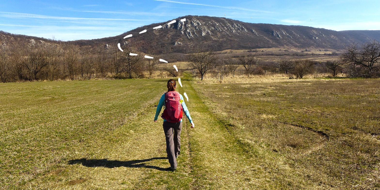 Hátizsákos turista gyalogol egy sziklás hegy felé