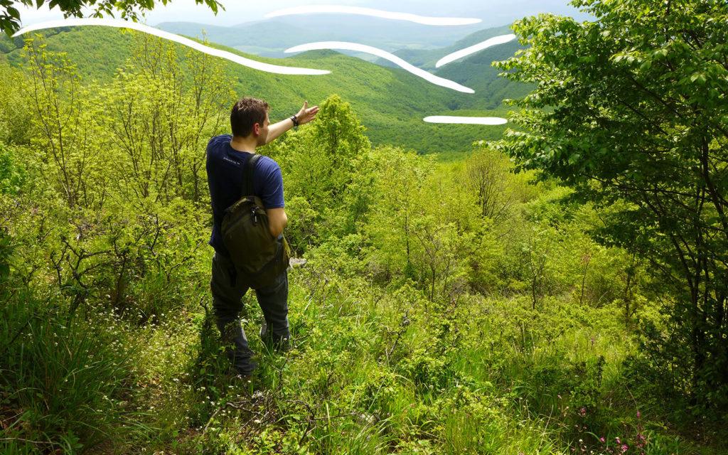 Egy férfi a távolba mutat egy hegy tetejéről